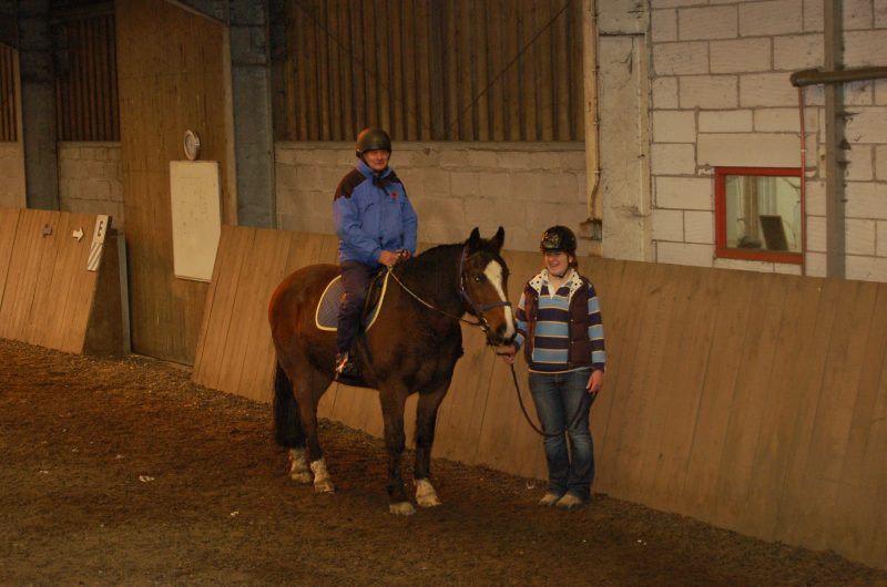Spud and volunteer helper in riding arena