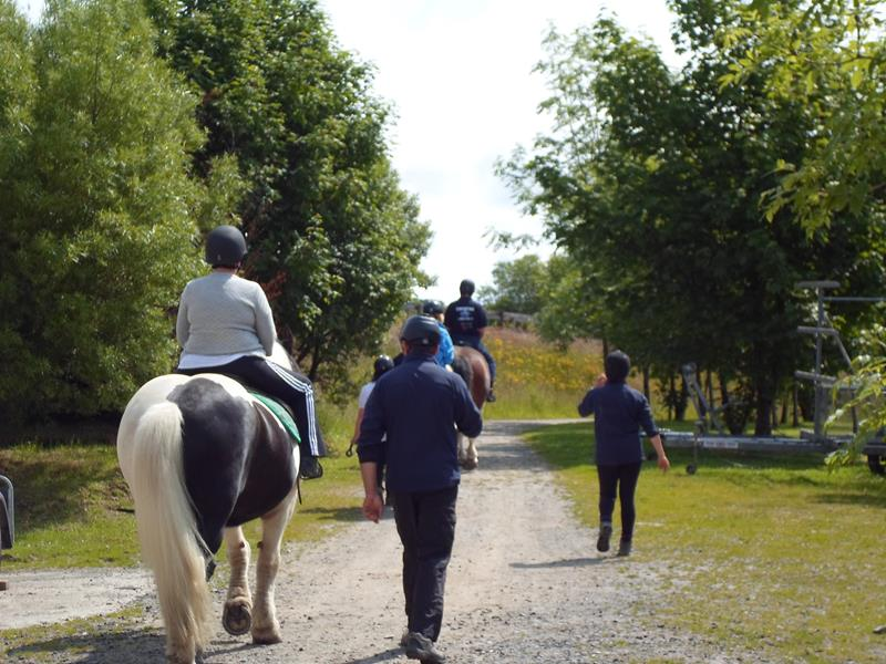 Kym riding along the path on Teddy
