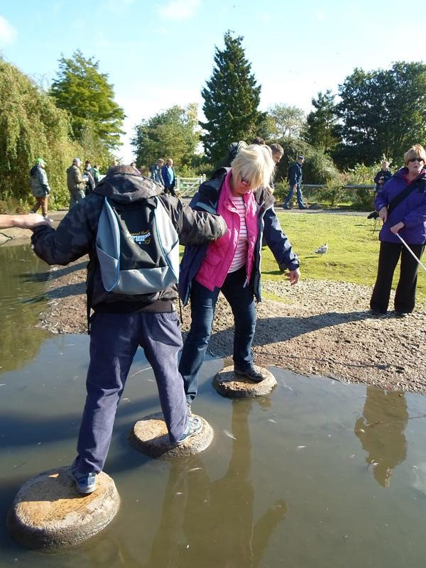 Andrew being helped by Jane to cross the stepping stones