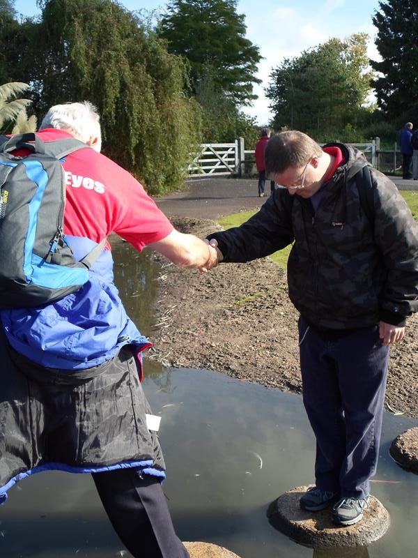 Spud helping Andrew across the stepping stones