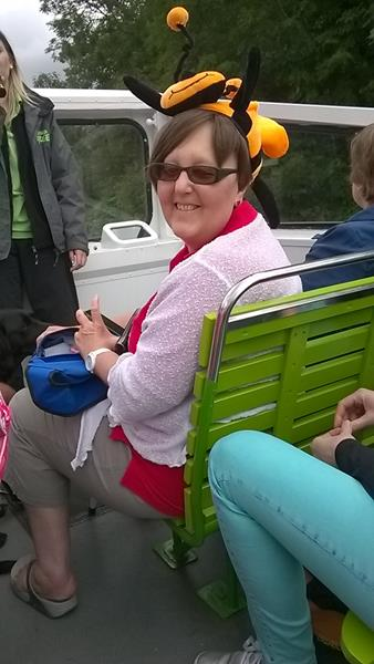 Kym wearing our bee hat on the open top tour bus