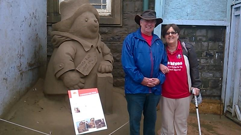 Kym and Russ stood beside Paddington Bear at the entrance to the exhibition