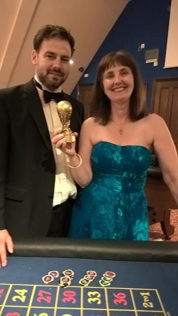 PETER, ONE OF THE CROUPIERS FROM DIAL A CASINO, STOOD WITH CLARE HOLDING HER TROPHY
